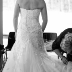 Mother fixing bride's dress